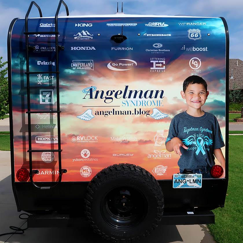 Photo of the back of an RV with the Angelman Syndrome logo and various sponsor logos.