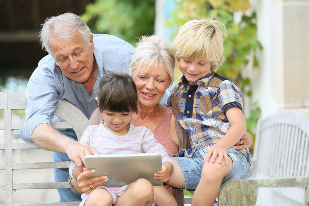Picture of grandparents enjoying internet content on a tablet with their grandchildren.