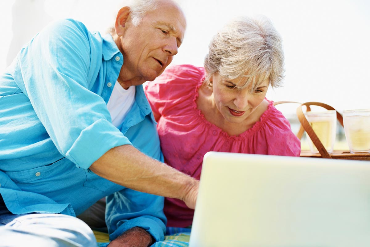 Photo of elderly couple surfing the internet on a laptop while outside enjoying a picnic.