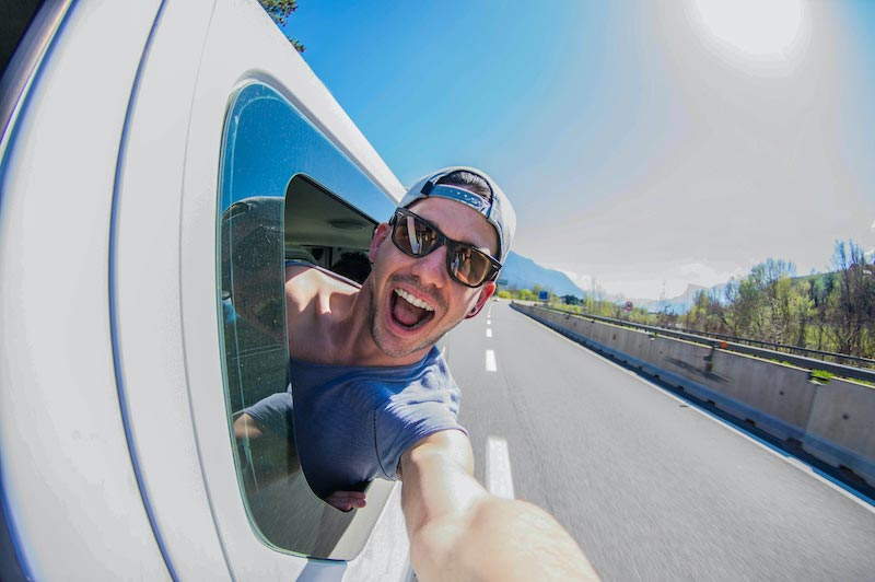 Photo of happy young man with his head of the vehicle window while traveling down the road.