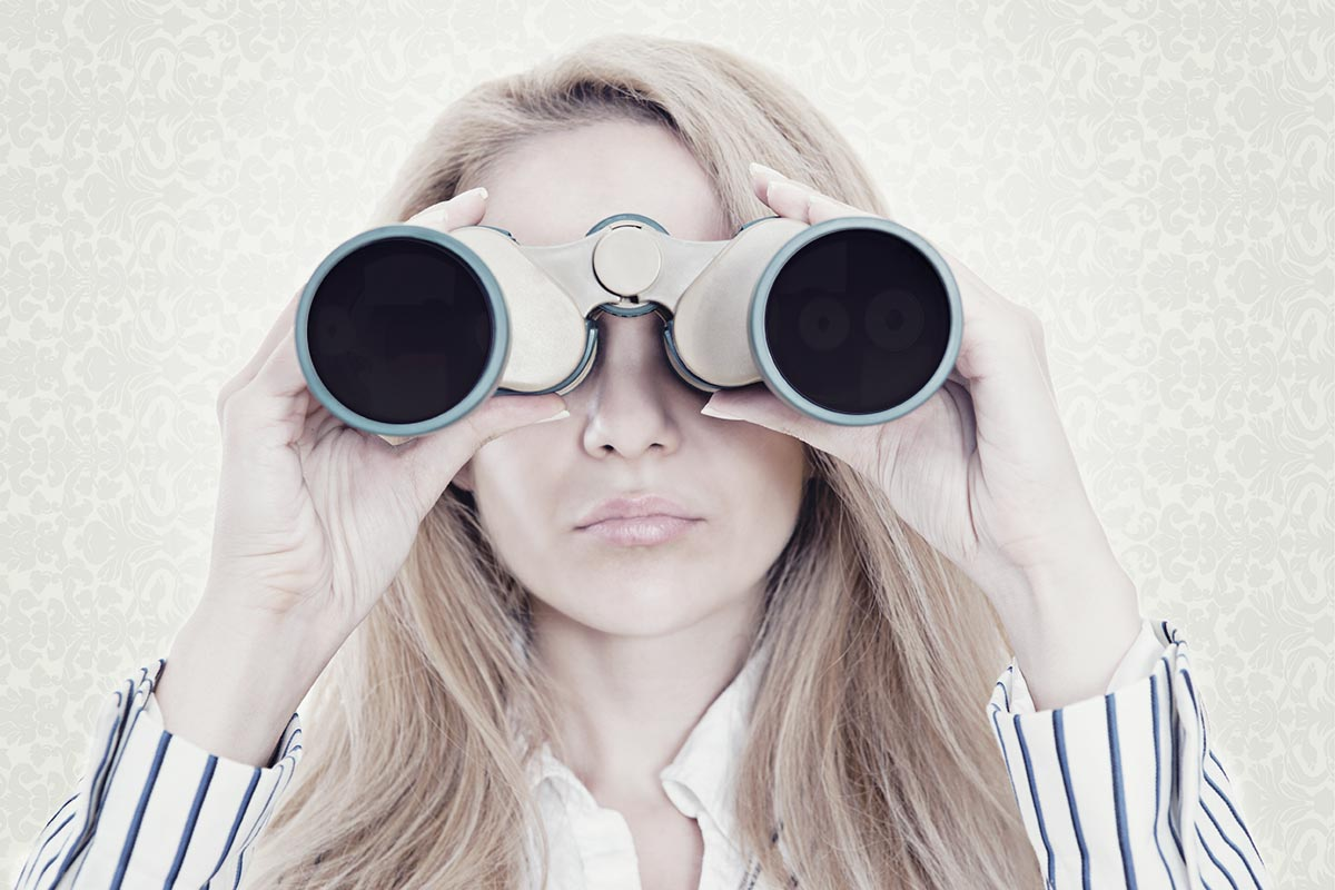 Photo of young woman looking through binoculars to see what is far away.